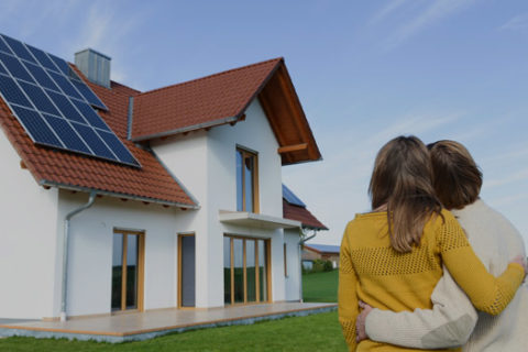 family looking up at solar panels on home