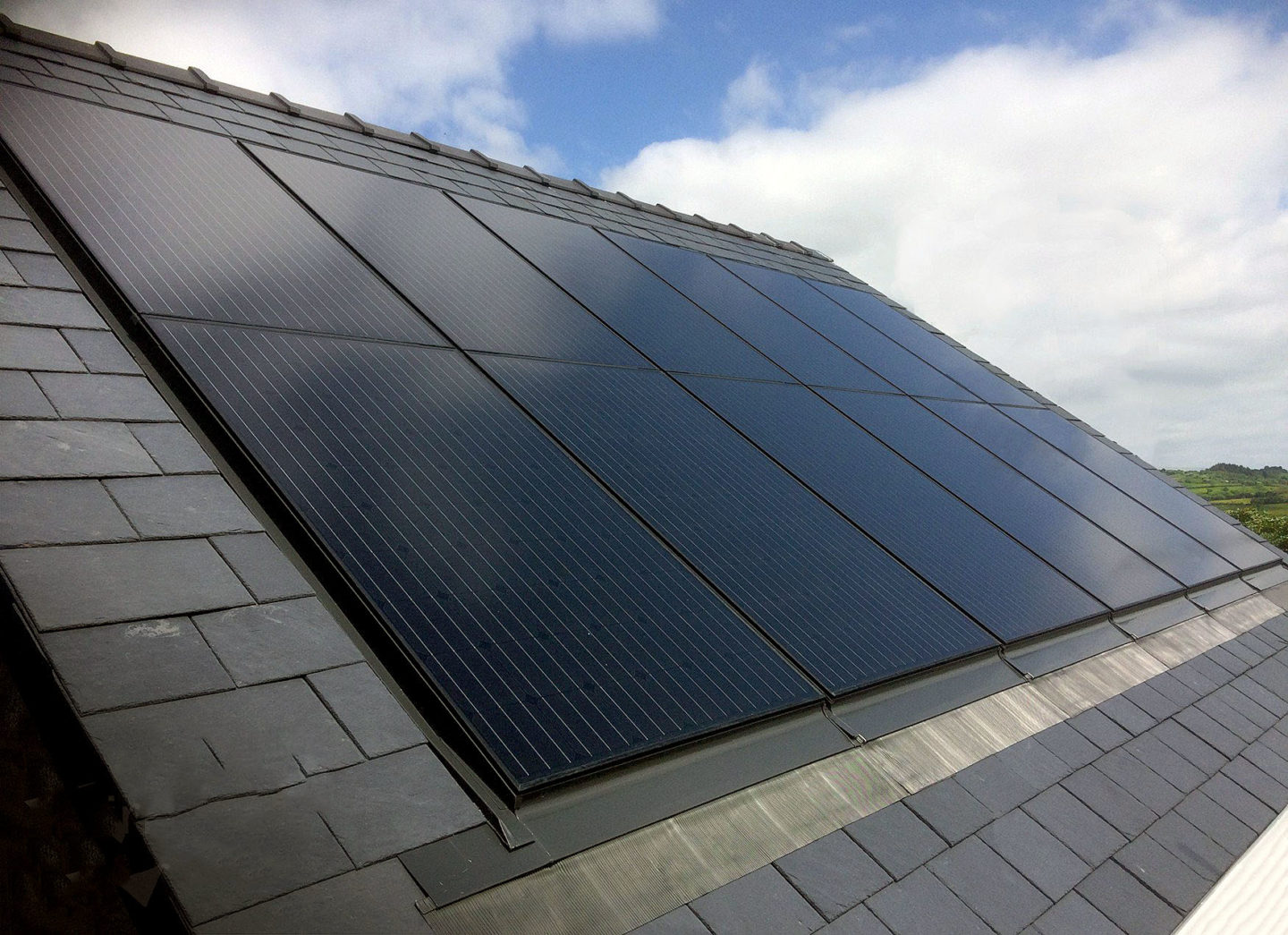 Black solar panels with clouds in background